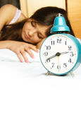 Sleeping girl with the alarm clock Royalty Free Stock Image