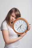 Sleeping girl with a big clock in his hands. Sleeping girl on a white background with a big clock in the hands of which 6.40 am Stock Photo