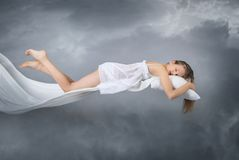 Sleeping girl. Flying in a dream. Clouds on grey background. Sleep royalty free stock photos
