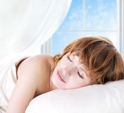 Sleeping girl in front of a winter window Stock Images