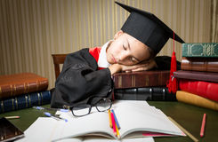 Sleeping girl in graduation cap lying on table full of books. Closeup portrait of sleeping girl in graduation cap lying on table full of books Royalty Free Stock Photography
