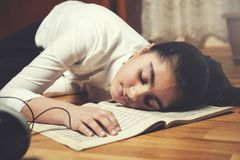 Sleeping girl on music book stock photography