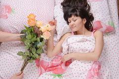 Sleeping girl presented with a bouquet of roses Royalty Free Stock Photos