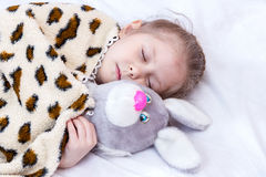 Sleeping girl with a toy hare Royalty Free Stock Photos