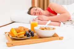 Sleeping girl and a tray with breakfast Stock Photos
