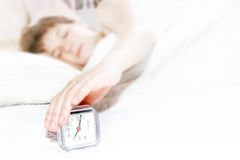 Sleeping girl trying to turn off the alarm clock Stock Image