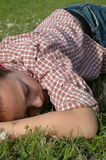 Sleeping on the grass. Young kid falling asleep in a spring meadow Royalty Free Stock Photo