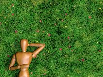 Sleeping on the grass. A wooden human figure is sleeping in grass lawn Royalty Free Stock Photos