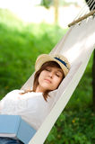 Sleeping on hammock. Young woman sleeping on hammock with open book Royalty Free Stock Image