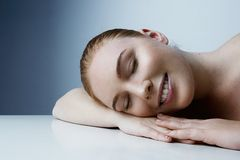 Sleeping handsome woman with fresh daily makeup and romantic smile. Healthcare girl concept. Close-up.  royalty free stock photo