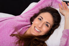 Sleeping. Happy young woman lying on her bed Royalty Free Stock Photos