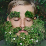 Sleeping hipster on grass with beard from moss Stock Photos