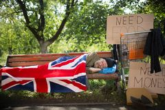 Sleeping homeless man covering with flag. Royalty Free Stock Photo