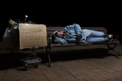 Sleeping Homeless. Homeless man at night sleeping on a park bench with his shopping cart full of his possessions Royalty Free Stock Image