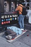 Sleeping Homeless NYC 1988 Tom Wurl. This was taken in Time Square, New York City, in 1988.  A person using a pay phone nearby, apparently oblivious, about what Stock Images