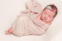 Sleeping infant newborn posing in pink gauze