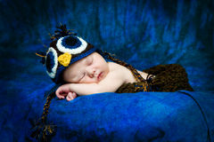 Sleeping Infant Wearing Crocheted Owl Hat. Artistic portrait of a newborn baby sleeping. The infant is wearing a crocheted owl hat in front of a blue, textured Stock Images