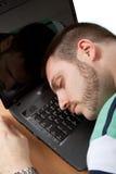 Sleeping on a Job. Tired man sleeping on a job on his notebook Royalty Free Stock Photo