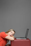 Sleeping on the job. Exhausted, overworked or lazy female employee resting her head on her arms in front of her laptop sleeping on the job, studio portrait on Royalty Free Stock Photo