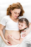 Sleeping kid girl embracing pregnant mother Stock Photos