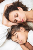 Sleeping kid girl and her mother in a bed. Royalty Free Stock Images
