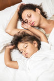 Sleeping kid girl and her mother in a bed. Royalty Free Stock Photo