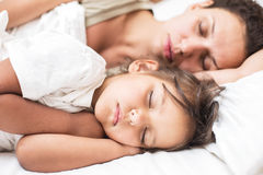 Sleeping kid girl and her mother in a bed. Stock Photography