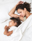 Sleeping kid girl and her mother in a bed. Royalty Free Stock Photography