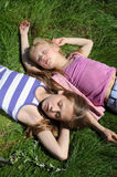 Sleeping kids. Two adorable little girls sleeping on the green grass Royalty Free Stock Image