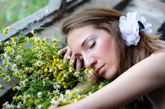 Sleeping lady with chamomile bouquet in spring Stock Photo