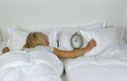 Sleeping Lady Covering Alarm Clock. Sleeping woman covering alarm clock with pillow which is showing nine o`clock and that she is late Stock Images