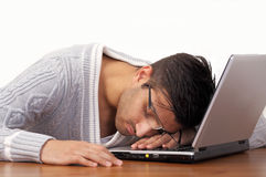 Sleeping on laptop. Tired young man sleeping with his head on a laptop Royalty Free Stock Images