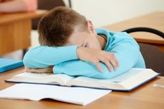 Sleeping at lesson. Cute schoolboy lying on book and sleeping in class during lesson stock images