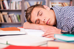 Sleeping in library. Handsome young man sleeping while sitting in library and leaning his face at the desk Royalty Free Stock Photos