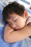 Sleeping Little Boy. Little boy sleeping on his arms royalty free stock images