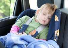 Sleeping little girl in car seat Royalty Free Stock Photos