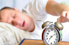 Sleeping man. A man is sleeping with an alarm clock in front Stock Photo