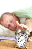 Sleeping man. A man is sleeping with an alarm clock in front Royalty Free Stock Photos