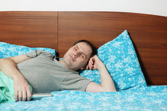 Sleeping man in bed stock images