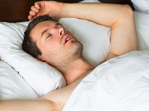Sleeping man in bed with his arm up Royalty Free Stock Image