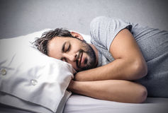 Sleeping man into bed. Sleeping man peacefully into bed Stock Images