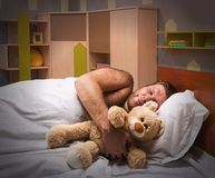 Sleeping man in bed with toy bear Stock Photos