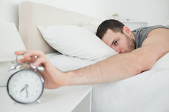 Sleeping man being awakened by an alarm clock. Sleeping attractive man being awakened by an alarm clock in his bedroom Royalty Free Stock Images