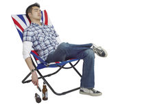 Sleeping man in a chair. Young Asian man asleep in a chair with a remote in his hand and beers on the floor Stock Images