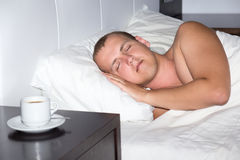 Sleeping man and cup of coffee Royalty Free Stock Photography