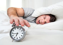 Sleeping man disturbed by alarm clock early mornin Stock Photo