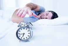 Sleeping man disturbed by alarm clock early mornin. Sleeping lazy man disturbed switching off alarm clock early morning Royalty Free Stock Image