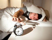 Sleeping man disturbed by alarm clock early mornin royalty free stock images