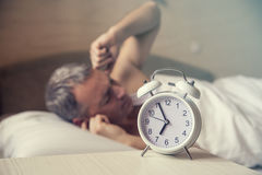 Sleeping man disturbed by alarm clock early morning. Angry man in bed awoken by a noise. Waked Up. Man lying in bed turning off an alarm clock in the morning stock image