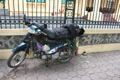 Sleeping man on his motobike on the street Royalty Free Stock Photography